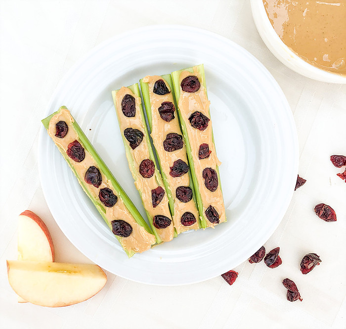Ants on a log with celery, peanut butter and topped with raisins