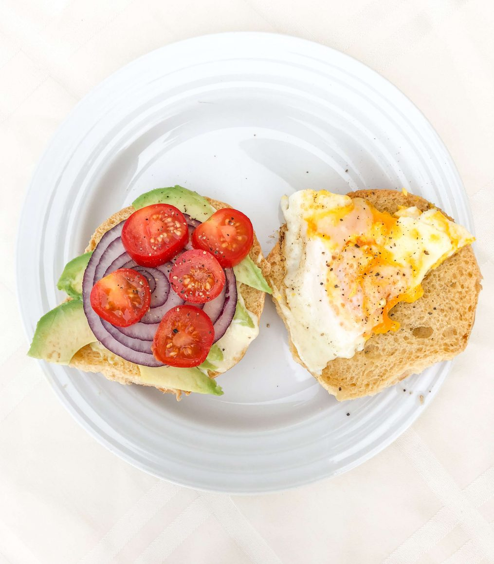 egg sandwich with tomatoes, onions, and avocado